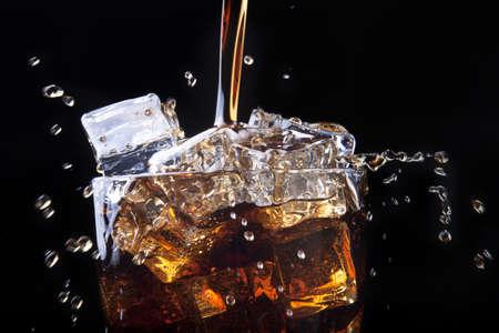 Vers cola drinken achtergrond met ijs en splash op een zwarte