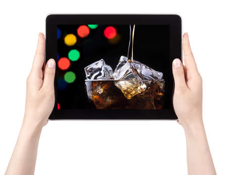 party background with splashing cola on a digital tablet with woman hands photo