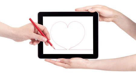 woman hand with pencil draws the heart on a tablet pc, isolated on a white background photo