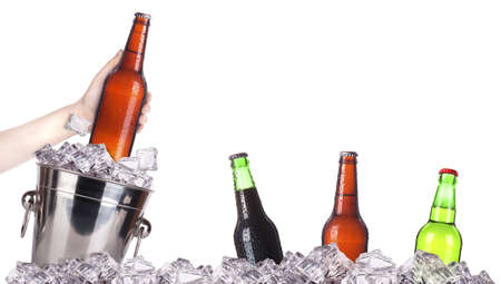 frosty beer with ice bucket and hand isolated on a white background photo