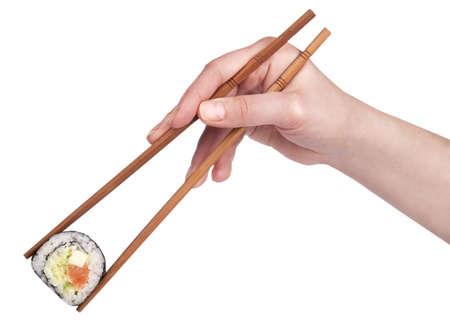 Sushi - roll op een zwarte plaat met vrouw hand geïsoleerd houden eetstokjes