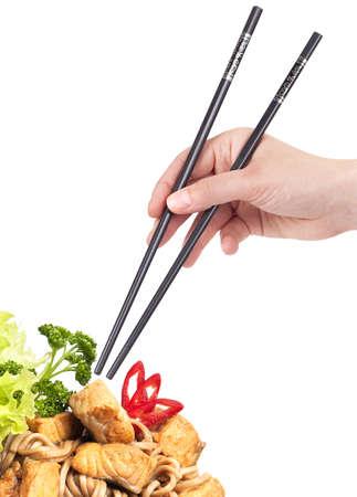 Noedels, vlees, groenten met de hand en en eetstokjes geïsoleerd Stockfoto