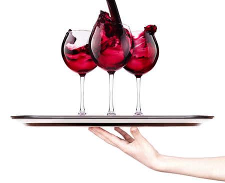 celebrar el día de fiesta de fondo - la mano con el vino rojo que salpica en una bandeja de plata