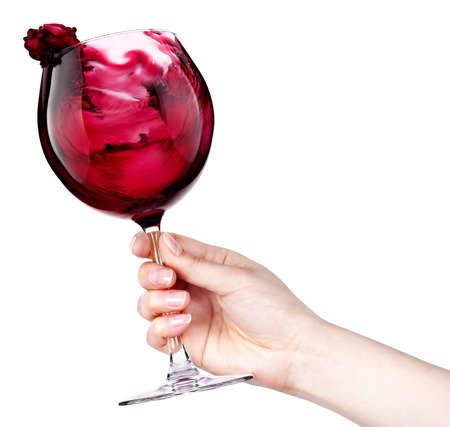 wine making: celebrate the holiday background - hand with red splashing wine making toast Stock Photo