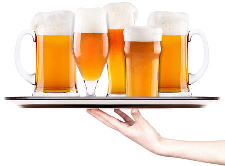 Frosty fresh beer collection with foam on a silver tray with waitress hand isolated photo