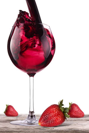 red wine splashing on a vintage wooden table with fresh red strawberry photo