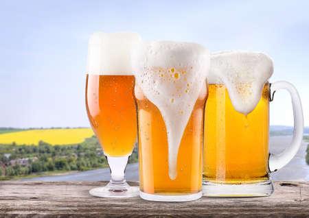 vasos de cerveza: Frosty de vidrio de cerveza ligera en una mesa de madera con escena de verano de fondo Foto de archivo