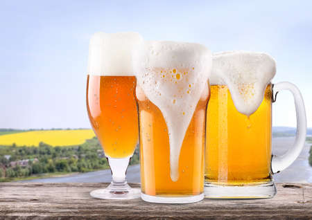 beer pint: Frosty glass of light beer on a wooden table with summer scene background