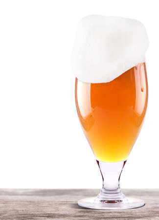 Frosty glass of light beer on a wooden table isolated on a white background photo