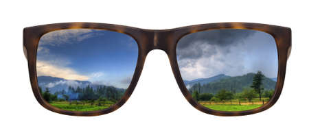Trendy sunglasses with a reflection of a beautiful landscape isolated on white photo