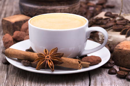 african coffee: white cup of espresso full of coffee roasted beans with plate on a wooden table Stock Photo