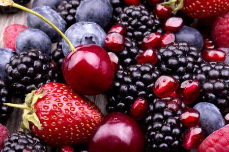 木製のテーブルに美味しい夏の果物。チェリー、ブルーベリー、ストロベリー、ラズベリー、ブラックベリー、ザクロ
