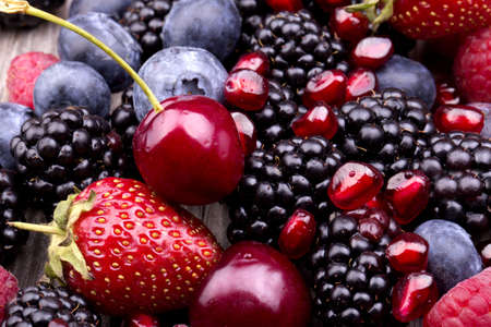 frutas: sabrosas frutas de verano en una mesa de madera. Cereza, moras azules, fresas, frambuesas, moras, granada
