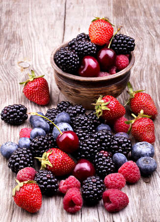 fruit drop:  tasty summer fruits on a wooden table. Cherry, Blue berries,  strawberry, raspberries, Blackberries, pomegranate