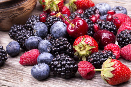 tasty summer fruits on a wooden table. Cherry, Blue berries,  strawberry, raspberries, Blackberries, pomegranate photo