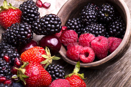 blackberry fruit:  tasty summer fruits on a wooden table. Cherry, Blue berries,  strawberry, raspberries, Blackberries, pomegranate