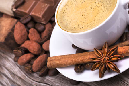 white cup of espresso full of coffee with Chocolate bar and spices on wooden table photo