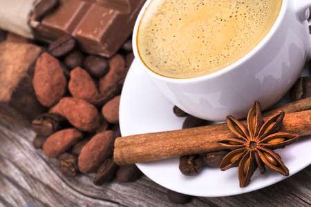 wit kopje espresso vol koffie met chocolade bar en kruiden op houten tafel