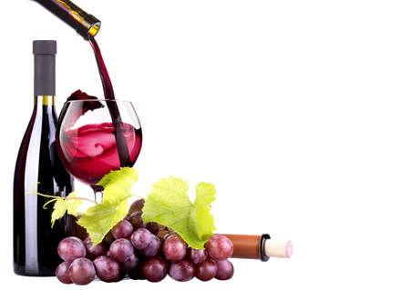 Rijpe druiven, glas wijn en een fles wijn op wit wordt geïsoleerd