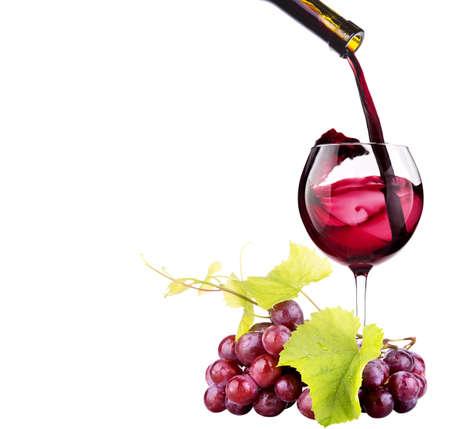Rijpe druiven en glas wijn op wit wordt geïsoleerd