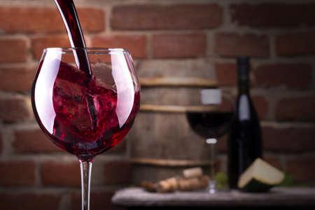 Glas wijn en wat fruit, een fles wijn, kaas tegen een bakstenen muur.