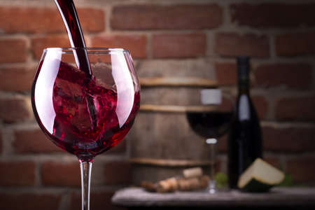 wine background: Glass of wine and some fruits, bottle of wine, cheese against a brick wall. Stock Photo