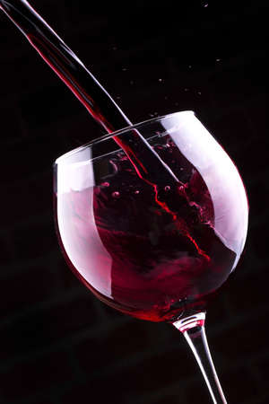 Splash red wine  against a black background photo