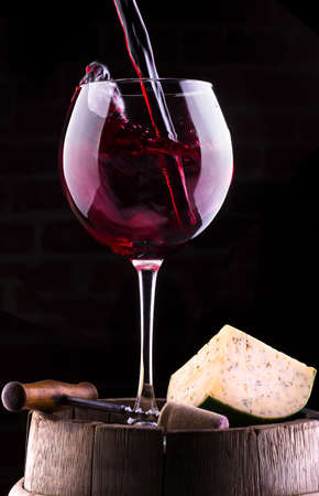 Splash red wine  against a black background on barrel with cheese, cork and corkscrew