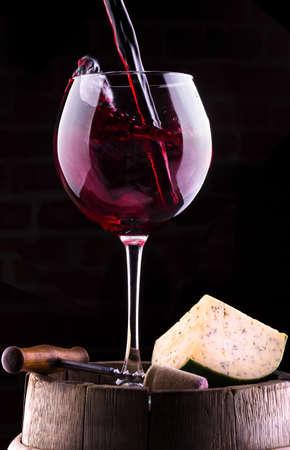 Splash rode wijn tegen een zwarte achtergrond op vat met kaas, kurk en kurkentrekker