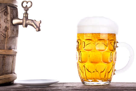 mug of ale: Glass of beer with barrel on a wooden table white background