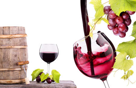 Red wine, glass barrel with grapes hand with glass over white photo