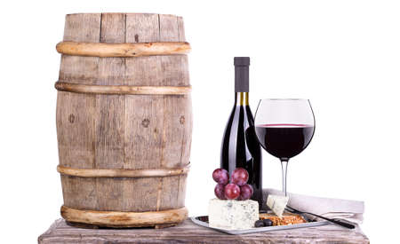 bottles and glass of wine, assortment of grapes and cheese cork on table isolated on white photo