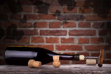 red wine and a bottle on a vintage wooden table against grunge brick wall background photo