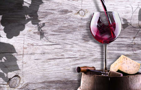 chease, corkscrew and wine glass on a wooden vintage barrel against grunge background photo