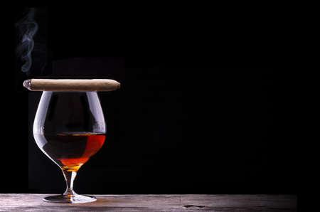 Cognac en sigaar op zwart met vintage tafel