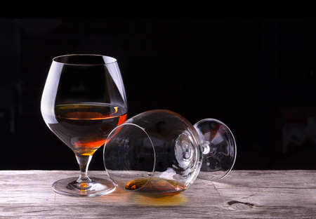 drunks: Cognac or brandy on a wooden table