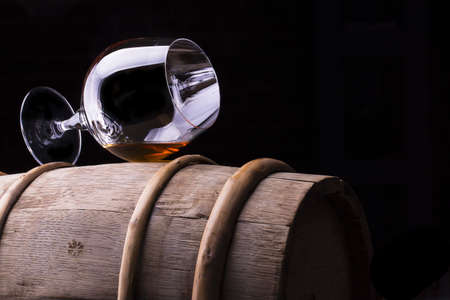 drunks: Cognac or brandy on a wooden barrel