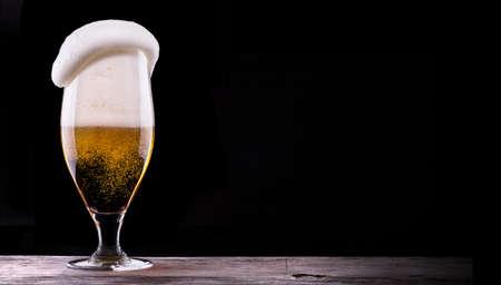 un bottled: Frosty glass of light beer on black background