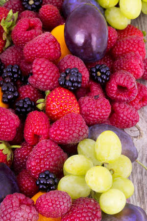 tasty summer fruits on a wooden table.  Strawberry, raspberriy, Blackberries, grapes,plum,Blue berries photo