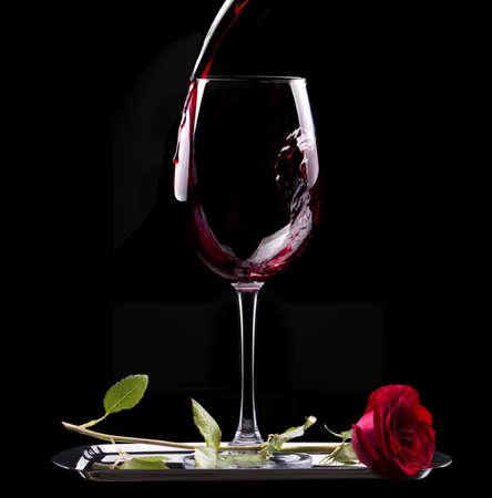 glas rode wijn en rode roos op zwarte achtergrond