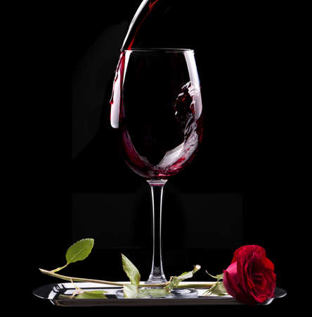 glass of red wine and red rose on black background