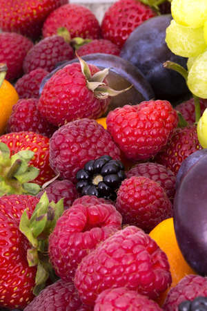 tasty summer fruits on a wooden table.  Strawberry, raspberry, blackberries, grapes, plum photo