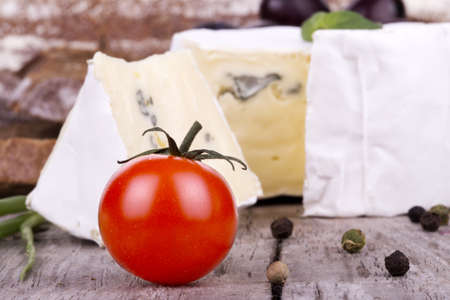 picnic lunch on a wooden board including a bread,cheese and cherry tomato photo