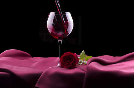 glass of red wine and red rose on black background photo