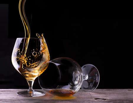 Cognac or brandy on a wooden vintage table with black background Standard-Bild