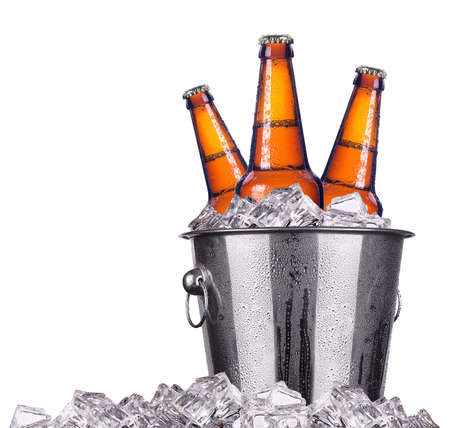 Botellas de cerveza en el cubo de hielo aislados en blanco