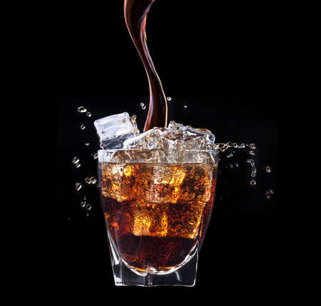 Fresh cola drink background with ice and splash on a black photo
