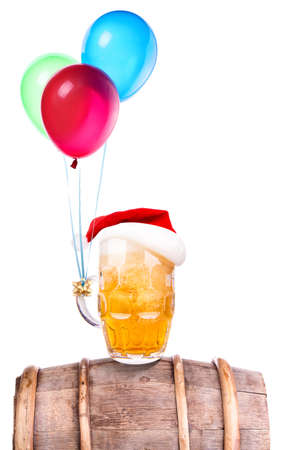 Beer with hat of Santa and flying balloons isolated on white photo