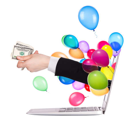 hand with money and balloons come out from a screen of a laptop computer isolated on white background photo