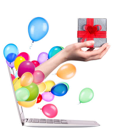 hand with a gift and balloons come out from a screen of a laptop computer isolated on white background photo